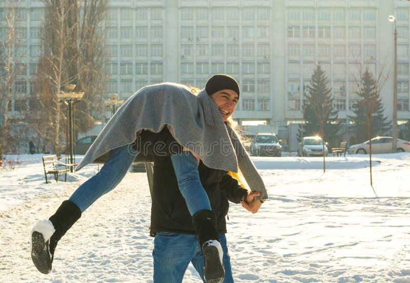 Il tipo e la ragazza si dedicano nell'inverno, la tiene sulle suoi spalle e giri Una coppia amorosa sta giocando fuori immagini stock