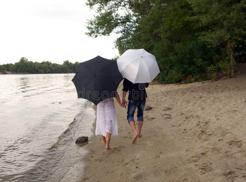 Il tipo e la ragazza sono sotto gli ombrelli fotografia stock libera da diritti