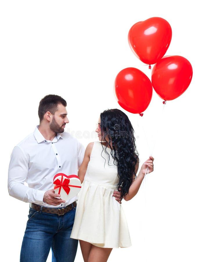 Il tipo elegante bello sta presentando un regalo a forma di cuore ed i palloni alla sua bella amica e sta sorridendo, biglietti d fotografia stock libera da diritti