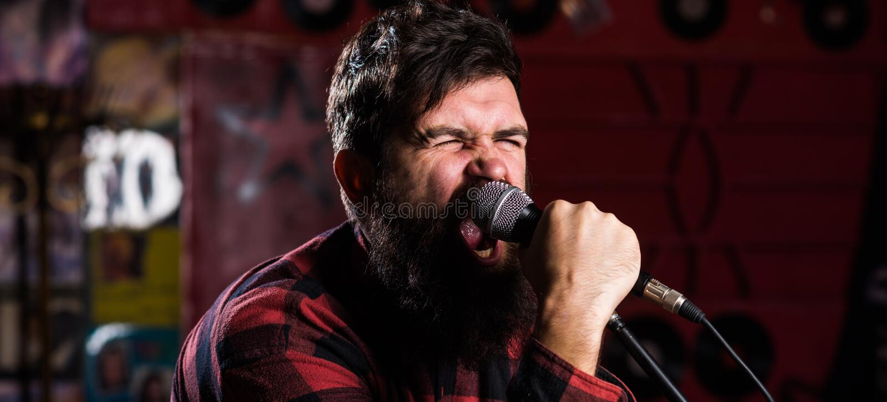 Il tipo gradisce cantare nel modo aggressivo Musicista con la canzone di canto dei baffi e della barba nel karaoke Concetto del r immagini stock