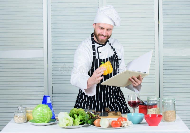 Il tipo ha letto le ricette del libro Concetto di arti culinarie L'uomo impara la ricetta Improve che cucina abilità Ultima guida fotografie stock