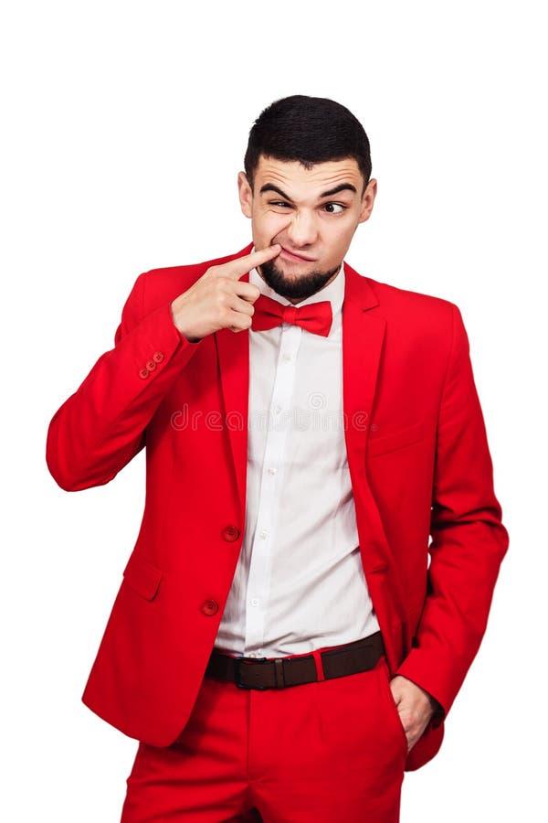 Il tipo ha qualcosa attaccato in suoi denti l'uomo divertente in un vestito rosso mostra un dito nella sua bocca fotografie stock