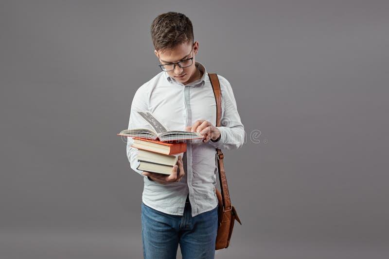 Il tipo intelligente in vetri vestiti in una camicia bianca con la borsa a tracolla marrone legge un libro su un fondo grigio fotografia stock