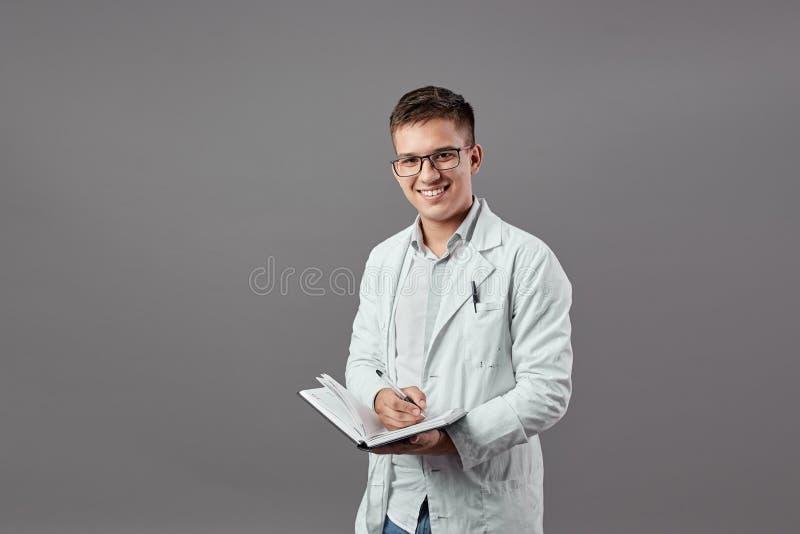 Il tipo intelligente in vetri vestiti in una camicia e nelle camice bianche fa le note in un taccuino su un fondo grigio immagine stock libera da diritti
