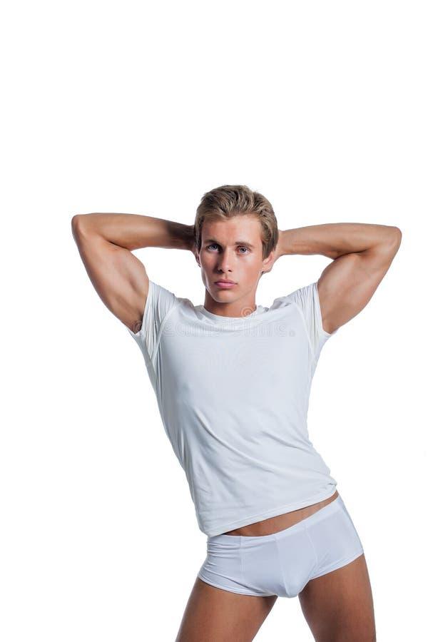 Il tipo muscoloso annuncia la biancheria intima, isolata su bianco fotografia stock
