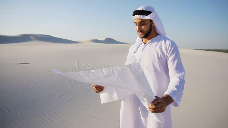Il tipo musulmano saggio della costruzione di sceicco dei UAE dell'Arabo ispeziona l'area fotografie stock