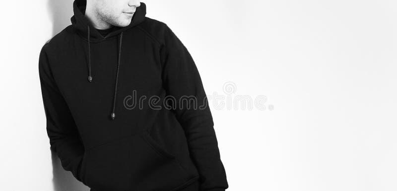 Il tipo nella maglia con cappuccio nera in bianco, maglietta felpata, supporto, sorridente sopra fotografia stock