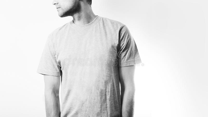Il tipo nella maglietta grigia e bianca in bianco, supporto, sorridente su un fondo bianco, derisione su, spazio libero, logo, pr fotografie stock libere da diritti