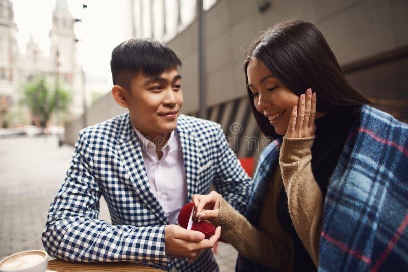 Il tipo presenta una proposta di nozze alla ragazza che si siede alla tavola in caffè immagini stock libere da diritti