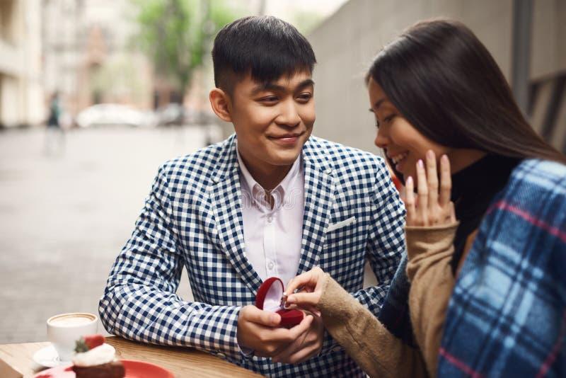 Il tipo presenta una proposta di nozze alla ragazza che si siede alla tavola in caffè fotografia stock libera da diritti