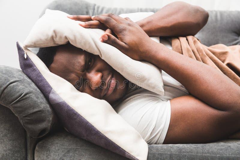 Il tipo sonnolento che sveglia presto dopo il segnale della sveglia di udienza e non vuole alzarsi fotografia stock libera da diritti