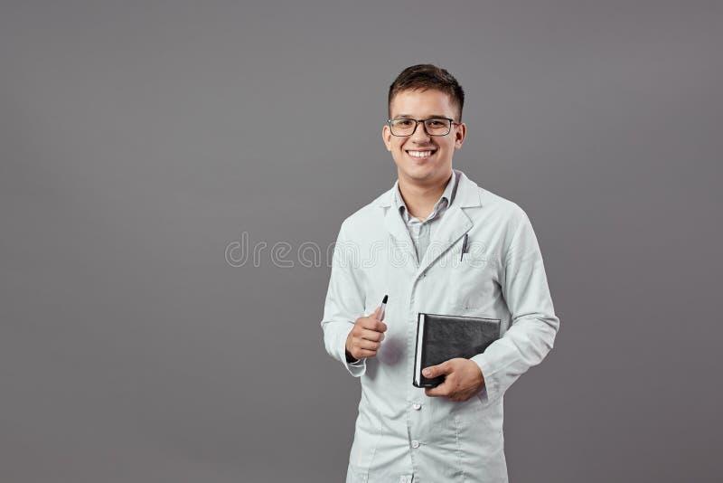 Il tipo sorridente intelligente in vetri vestiti nelle camice sta tenendo un taccuino e una pentola su un fondo grigio fotografie stock libere da diritti