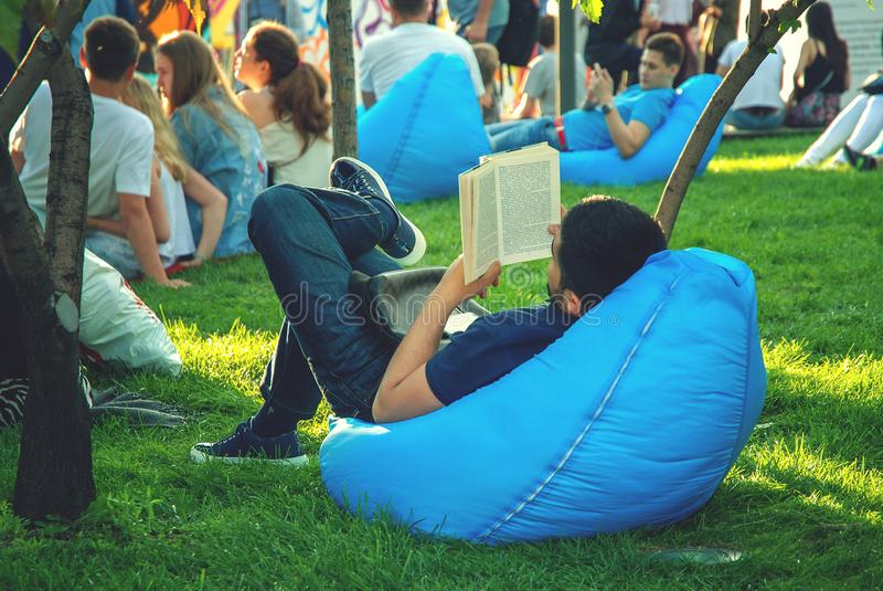Il tipo sta leggendo un libro nel parco fotografia stock
