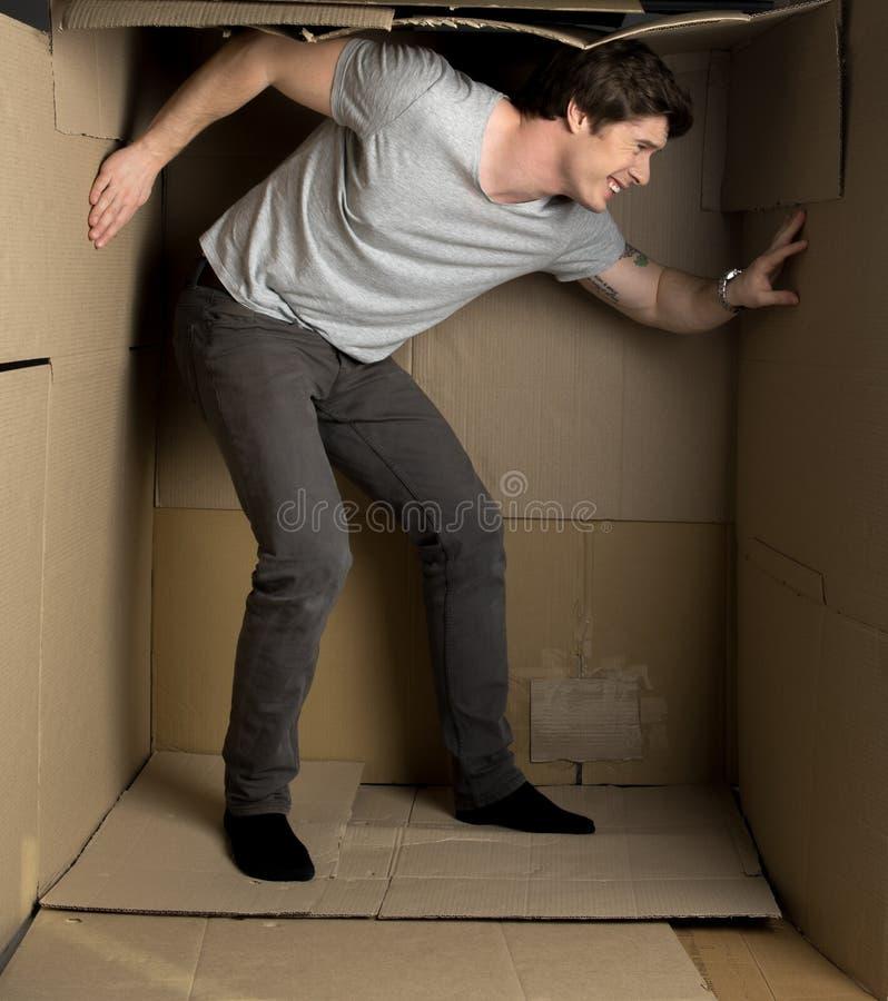 Il tipo sta ritenendo il disagio dentro il contenitore di carta fotografie stock libere da diritti