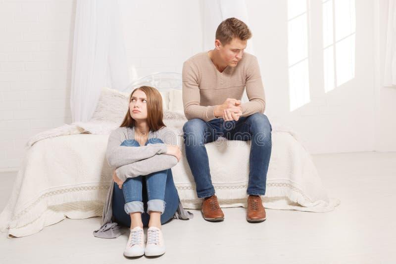 Il tipo sta sedendosi sul letto e la ragazza sul pavimento non sta parlando l'un l'altro all'interno fotografia stock libera da diritti