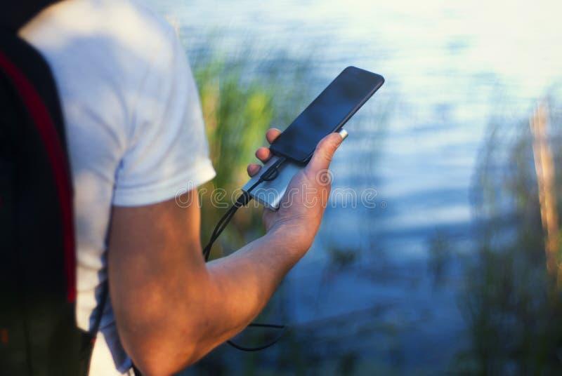Il tipo sta tenendo un caricatore portatile con uno smartphone in sua mano Uomo su un fondo della natura con una pianta e un lago fotografia stock libera da diritti