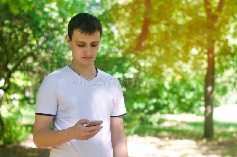 Il tipo sta tenendo uno smartphone mobile in parco e sta esaminando lo schermo dipendenza del telefono, reti sociali lavoro sull' fotografie stock libere da diritti