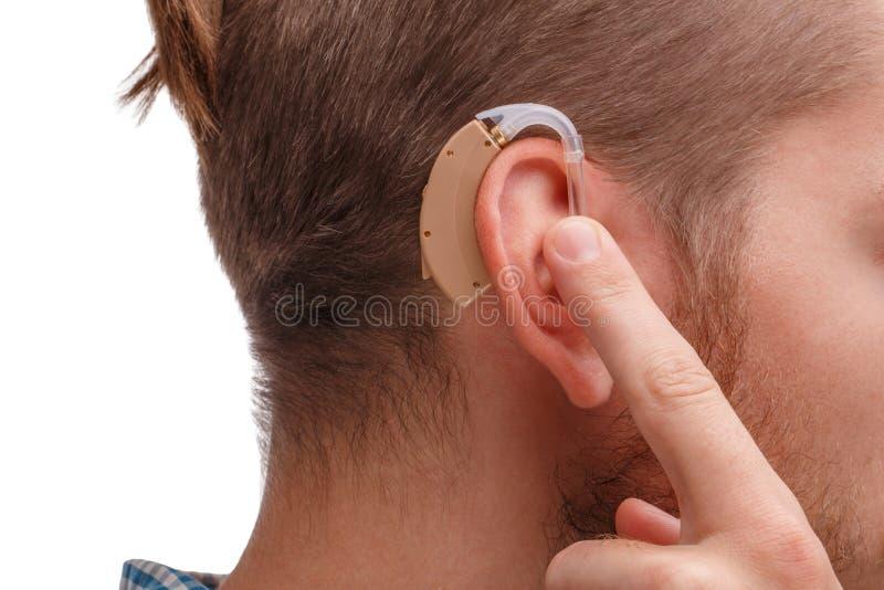 Il tipo tiene il dito della protesi acustica sul suo orecchio Isolato fotografie stock