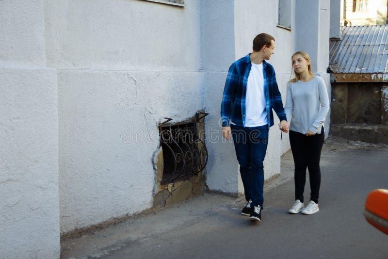 Il tipo tira la mano della ragazza, lo persuade che andare con lui, la ragazza non vuole a, sguardi al tipo con un piercing fotografie stock libere da diritti