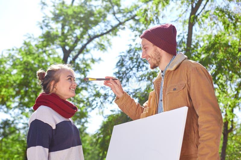 Il tipo tocca il naso del ` s dell'artista con una spazzola immagini stock libere da diritti
