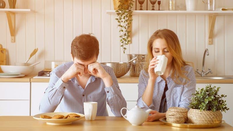 Il tipo triste della ragazza delle coppie ha silenziosamente tè bevente della prima colazione fotografie stock libere da diritti