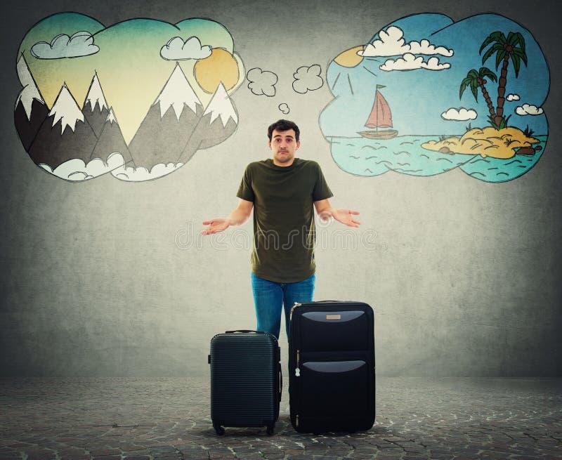 Il tipo turistico sconcertato ha problemi per scegliere la destinazione di vacanza fra il mare ed il viaggio delle montagne fotografia stock libera da diritti