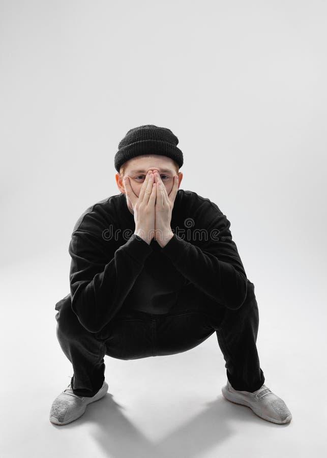 Il tipo vestito in jeans neri, maglietta felpata, cappello e scarpe da tennis grige è occupante e vicino il suo fronte con le su fotografia stock libera da diritti