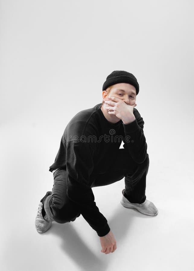 Il tipo vestito in jeans neri, maglietta felpata, cappello e scarpe da tennis grige è occupante e vicino il suo fronte con le su immagine stock libera da diritti