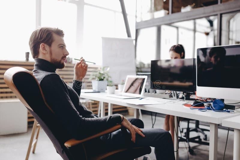 Il tipo vestito in vestiti casuali di stile dell'ufficio sta sedendosi in una sedia dell'ufficio allo scrittorio nell'ufficio mod fotografia stock libera da diritti