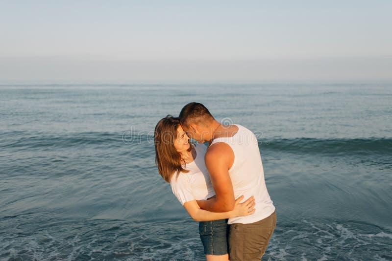 Il tipo vicino al mare abbraccia la ragazza fotografia stock