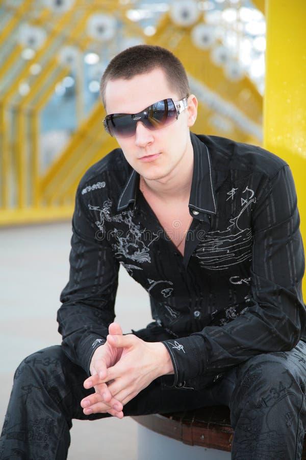 Il tirante in occhiali da sole si siede sulla passerella fotografie stock