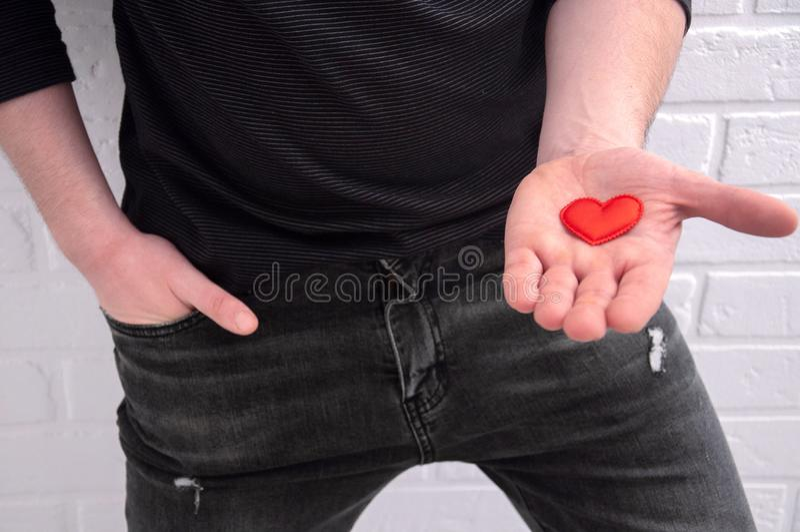 Il tizio tiene il cuore in mano Il tizio dichiara il suo amore Congratulazioni per San Valentino fotografia stock