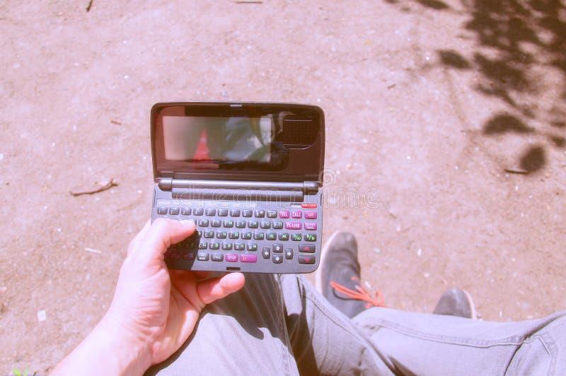 Il tizio tiene in mano un vecchio microcomputer Dispositivo obsoleto fotografia stock libera da diritti