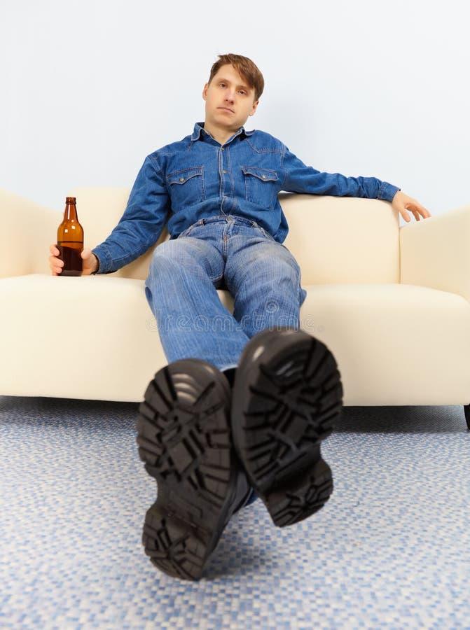 Il tizio ubriaco ha seduto scompostamente sullo strato immagine stock libera da diritti