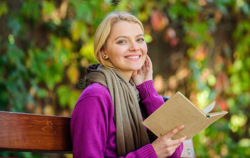 Il topo di biblioteca di signora ha letto il libro all'aperto cade il giorno La ragazza si siede il banco che si rilassa con il f immagine stock libera da diritti