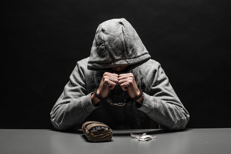Il tossicomane è stato arrestato per uso della droga alla tavola soffrendo dalla dipendenza su un fondo nero scuro fotografia stock libera da diritti