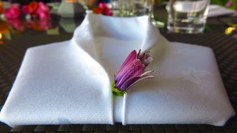 Il tovagliolo di tela bianco ha piegato in forma della camicia dello smoking immagine stock libera da diritti
