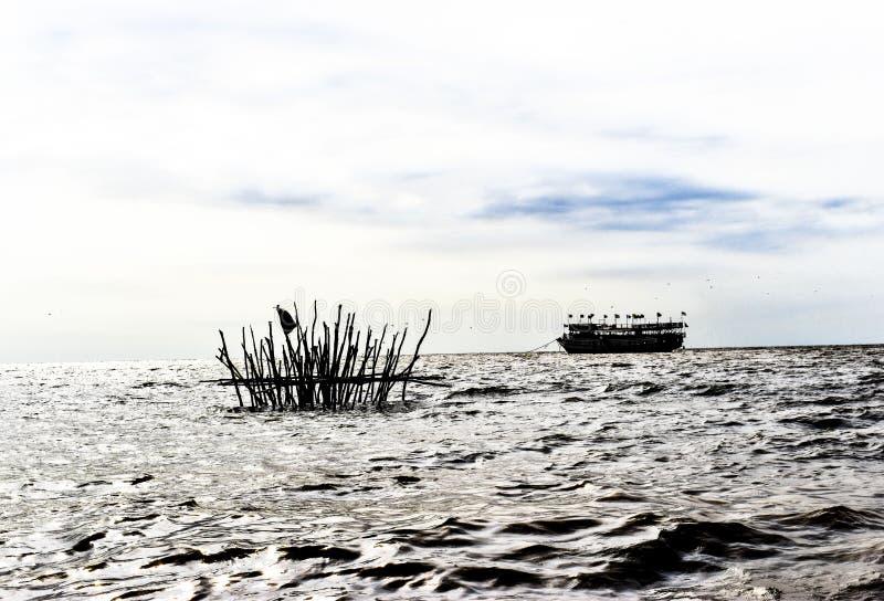 Il traghetto è trattenuto da un'ancora improvvisata mentre il sole splende sul lago Tonle Sap in Cambogia fotografie stock libere da diritti