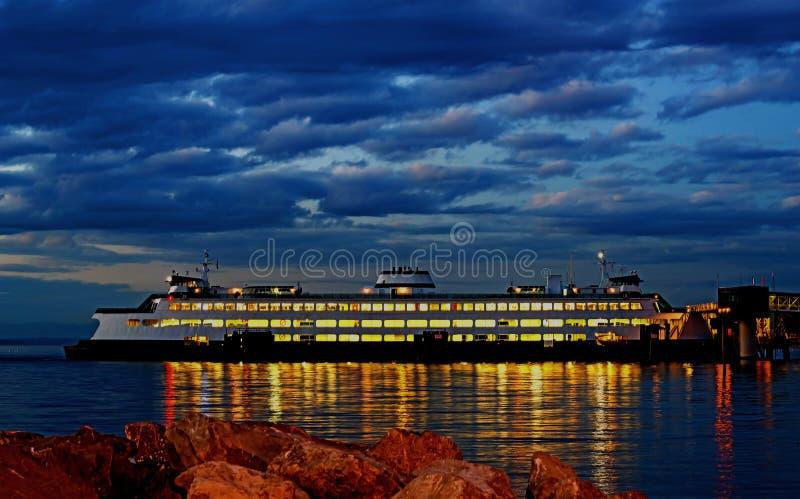Il traghetto di trasporto di persone e dell'automobile si è messo in bacino in pilastro alla notte immagini stock