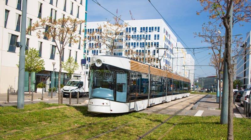 Il tram in mezzo alla città rotola sul prato inglese immagini stock