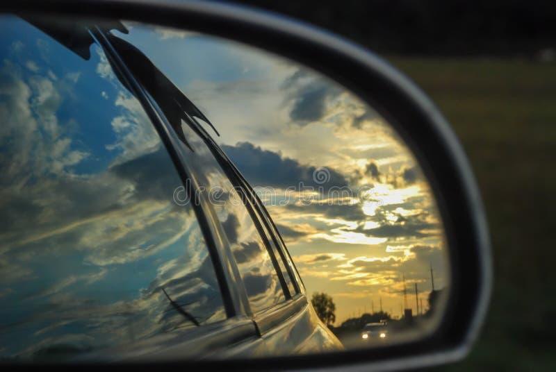 Il tramonto è riflesso nel retrovisore di un'automobile immagini stock