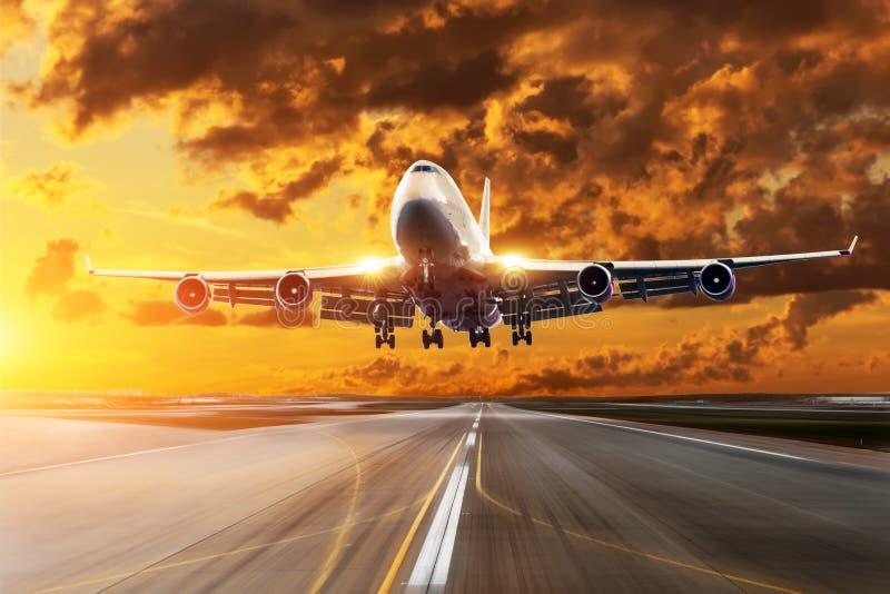Il tramonto arancio di contrapposizione nel cielo sopra l'aeroplano in ascesa all'aeroporto fotografia stock