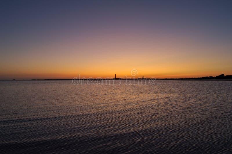 Il tramonto arancione che scorre sull'oceano immagine stock libera da diritti