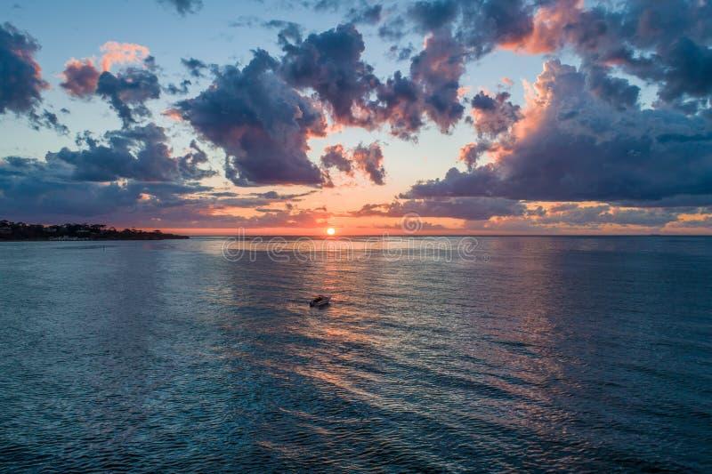 Il tramonto con una barca sola, navigante la traccia leggera immagini stock libere da diritti