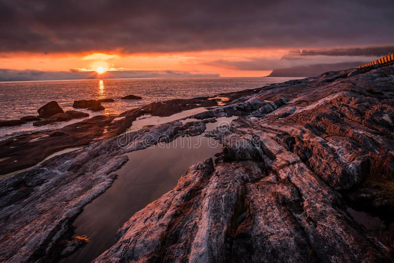 Il tramonto drammatico e ardente sopra la riva rocciosa con acqua sguazza immagine stock