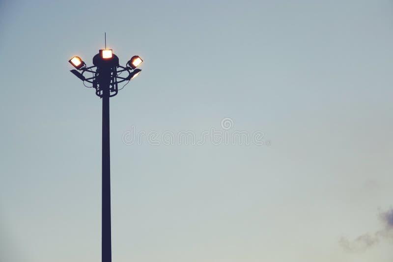 Il tramonto e l'albero alto con le luci di inondazione agli sport parcheggiano fotografia stock