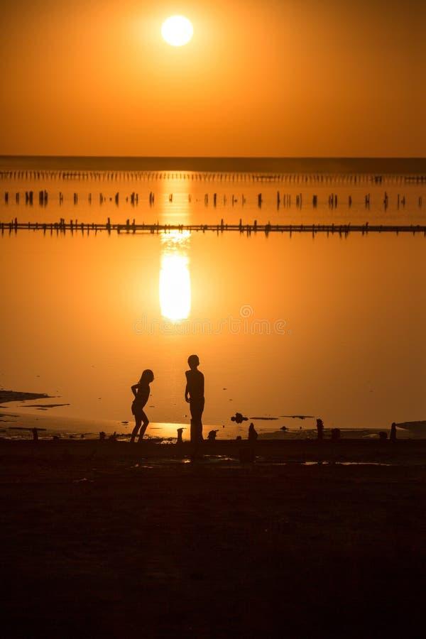 il tramonto mette sopra l'orizzonte ed è riflesso sulla superficie di un lago di sale la gente cammina e raccoglie il sale fotografia stock libera da diritti