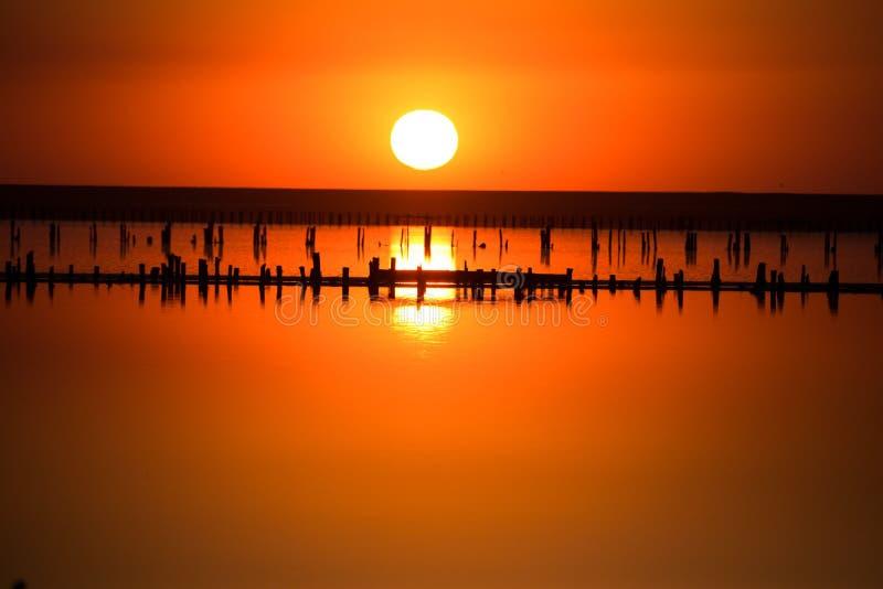 il tramonto mette sopra l'orizzonte ed è riflesso sulla superficie di un lago di sale la gente cammina e raccoglie il sale fotografie stock libere da diritti
