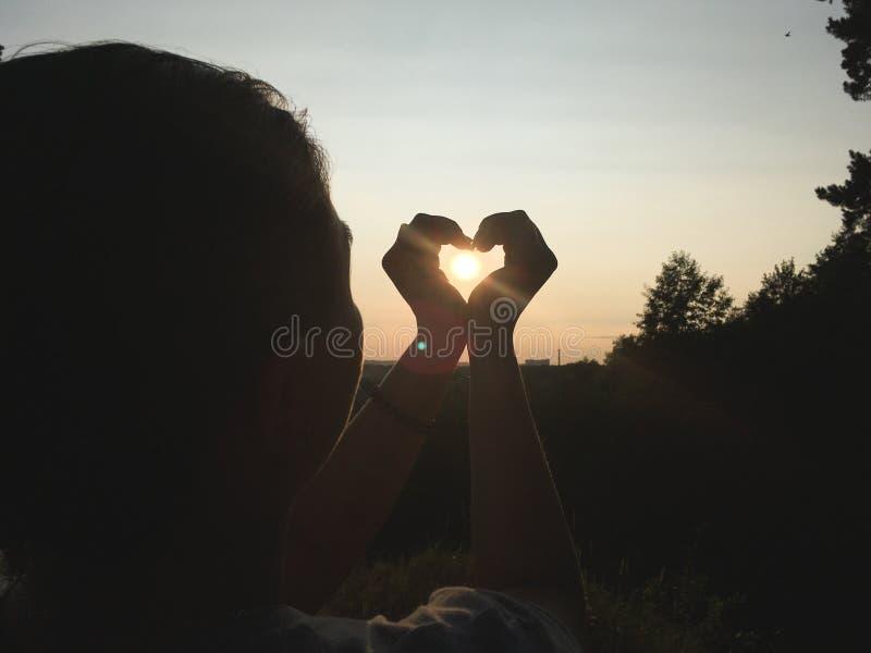Il tramonto nella mano del ` s della ragazza fotografia stock