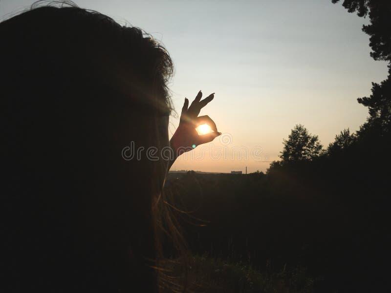 Il tramonto nella mano del ` s della ragazza immagini stock libere da diritti